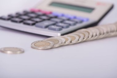 Stack of coins and calculator on white background.