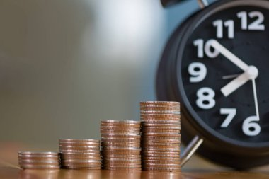 Alarm clock and step of coins stacks on working table, time for
