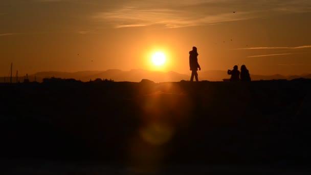 Sagoma di persone a guardare un tramonto arancione