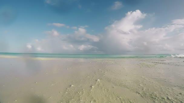 Pláž, moře, písek, vlny, modrá obloha, mraky na tropickém ostrově Malediv. Indický oceán a krásná pláž Paradise