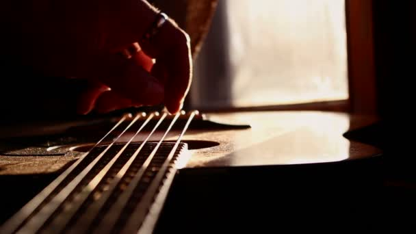 Guitarist Tuning and Checking Acoustic Guitar in Music Studio at Sunset
