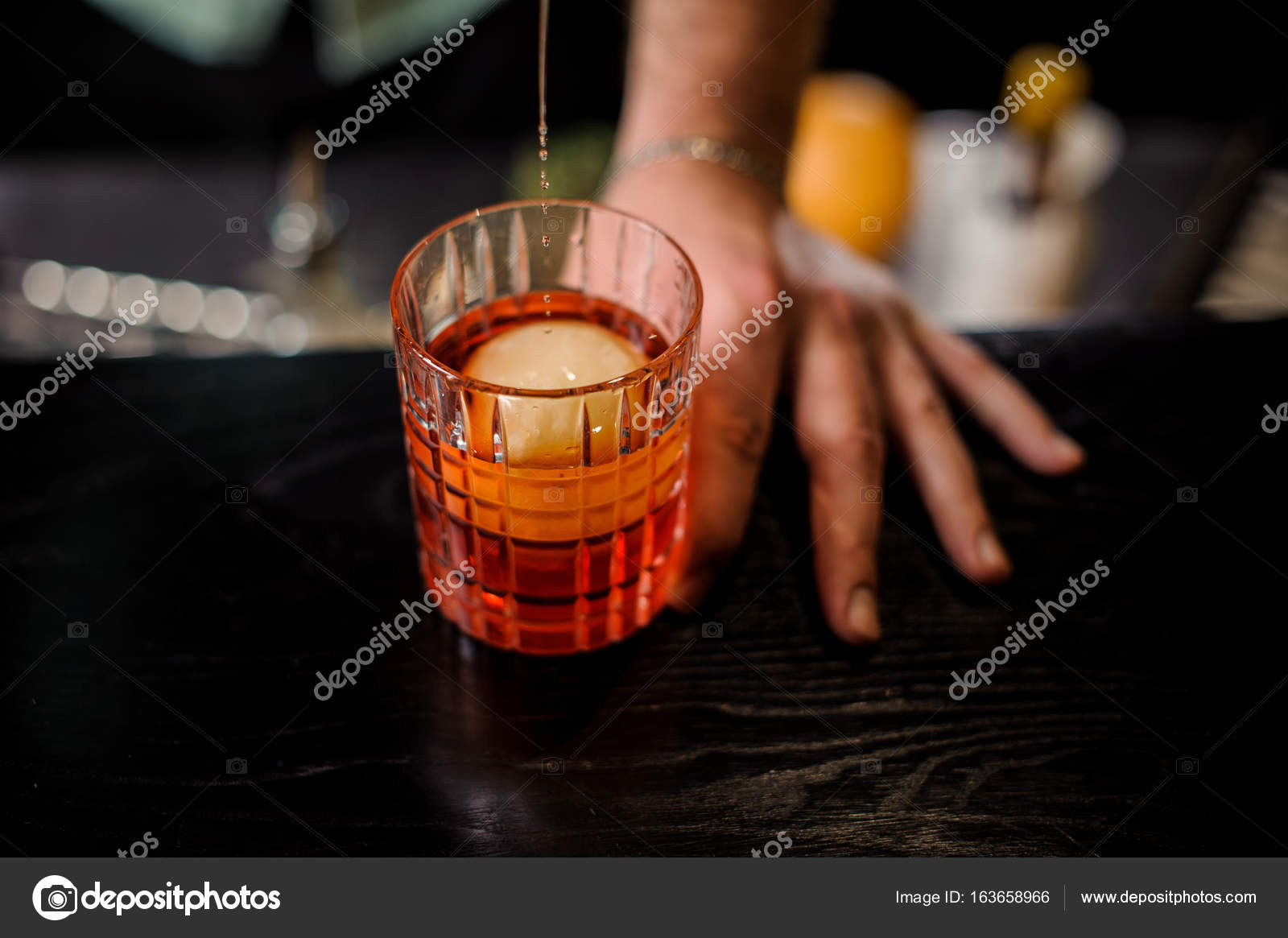 5f8d11eb18 Chiuda il barista versando il cocktail rosso nel bicchiere con ghiaccio  palla — Foto di Fesenko