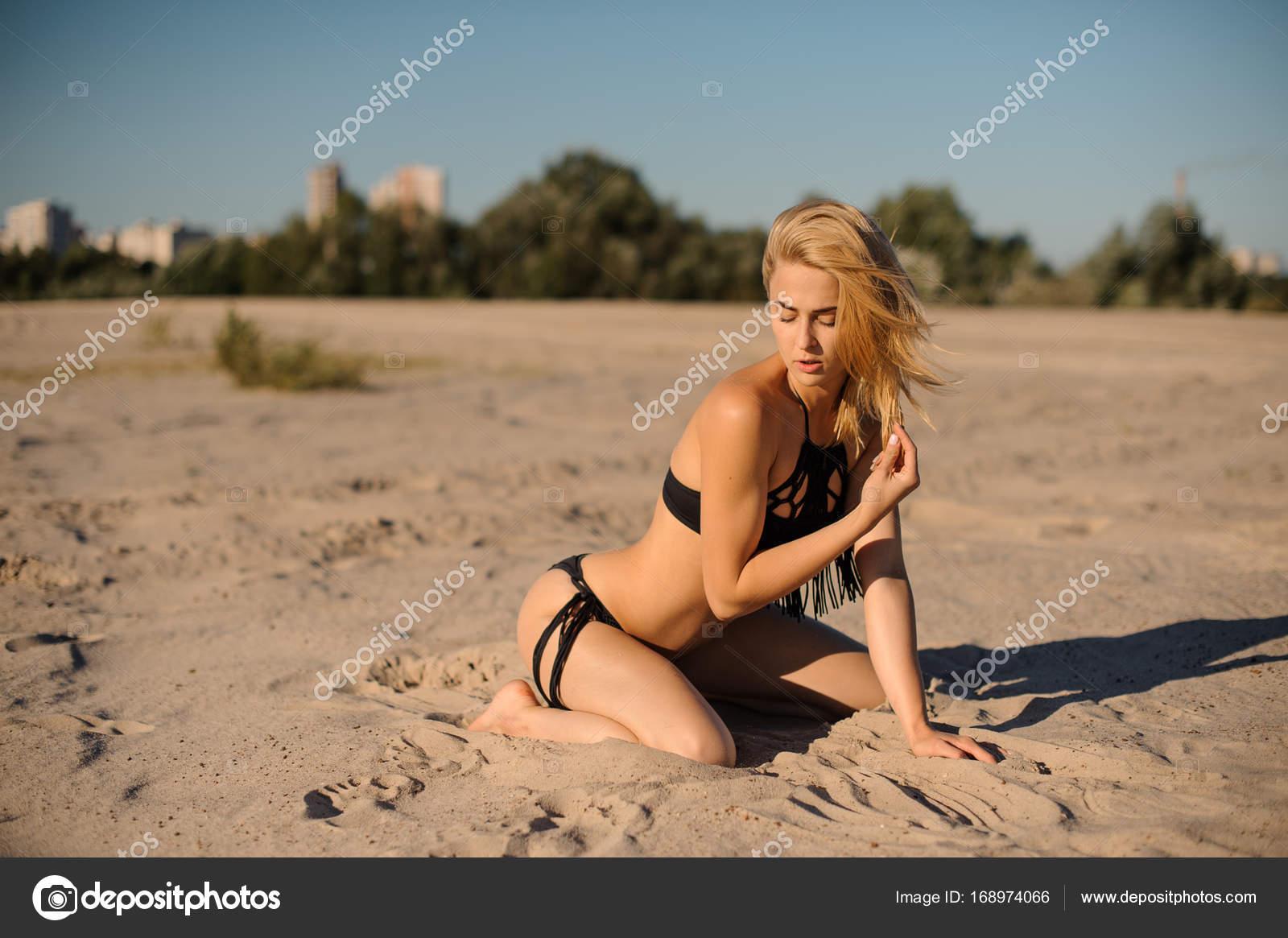 d8d876060d9d Mujer sexy en traje de baño negro sentado en la arena — Fotos de ...