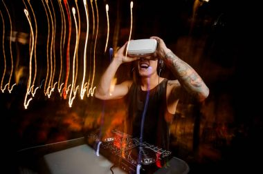 Young DJ in virtual reality glasses plays the track in club