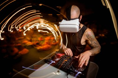 Male DJ in glasses of virtual reality in the process of work