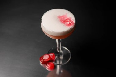 Cocktail glass with sweet alcoholic drink decorated with pink candies