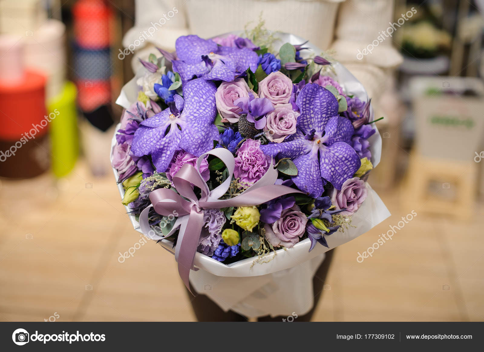 Woman In A White Sweater Holding A Large Flower Bouquet In Purple