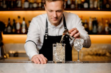 Young barman dressed in a white shirt pouring alcoholic drink into a glass with ice cubes