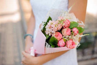 woman holds a bouquet of pion-shaped roses, astilba and roses