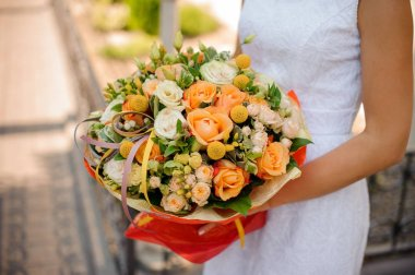 woman holds a bouquet of kraspedia, roses, pion-shaped roses and succulents