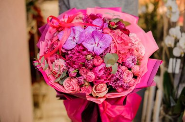 girl holds a bouquet of peonies, roses and orchids decorated with eucalyptus