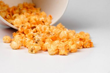 Macrophotograpy of fresh and warm tasty salt popcorn in a white paper bucket