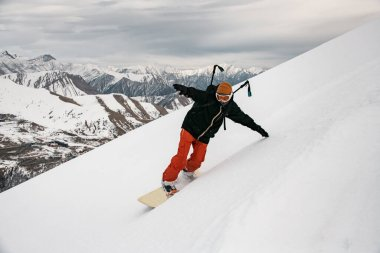 man snowboarder in bright clothes moving down the mountain.