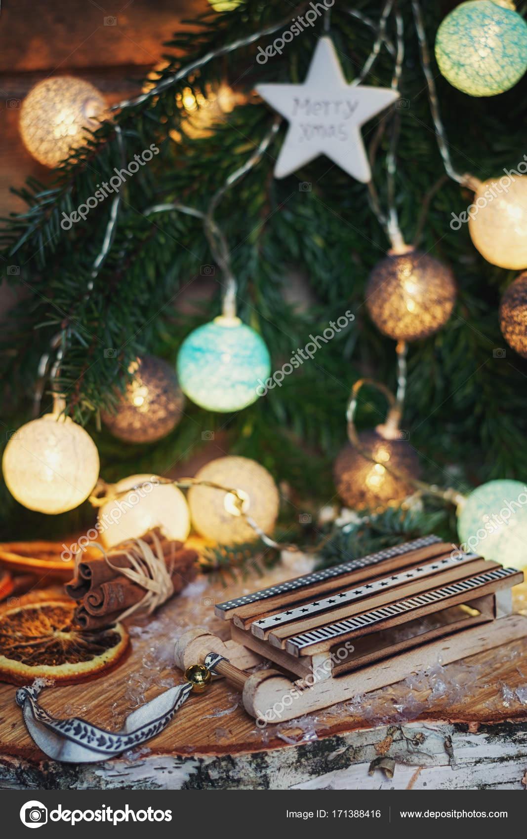 Beleuchtete Christbaumkugeln.Kleine Bunte Holzschlitten Vor Ein Weihnachts Zweig Mit Beleuchtete