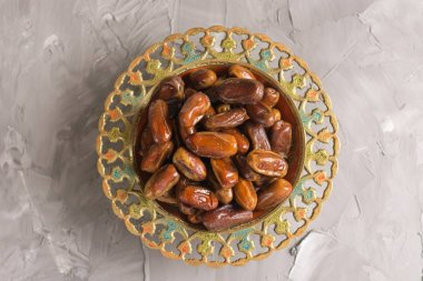 An ornamental bowl of Arabian dates. Top view.