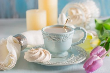Coffee with milk in the light blue china cup on the wooden background with lilac tulip and white napkin.