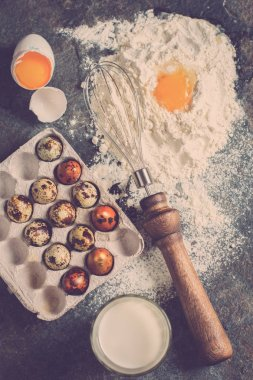 Baking ingredients. Flour, eggs, milk in the glass, quail eggs, eggbeater on a black stone texture from above. Flat lay. Rustic style.