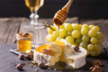 Camembert with grapes nuts and pouring honey on the stone tray.
