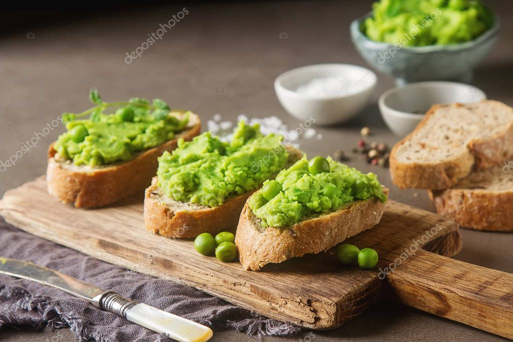 Baguette with mashed green peas and mint. Dark background. Selec