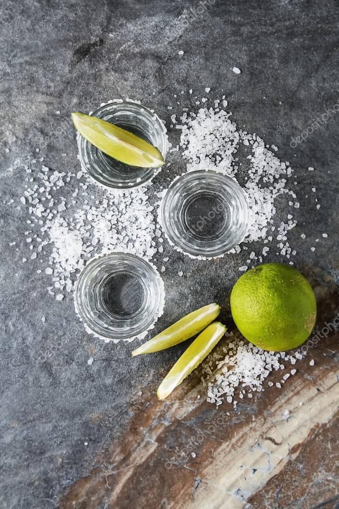 Tequila silver with lime and sea salt. Dark background. Selectiv