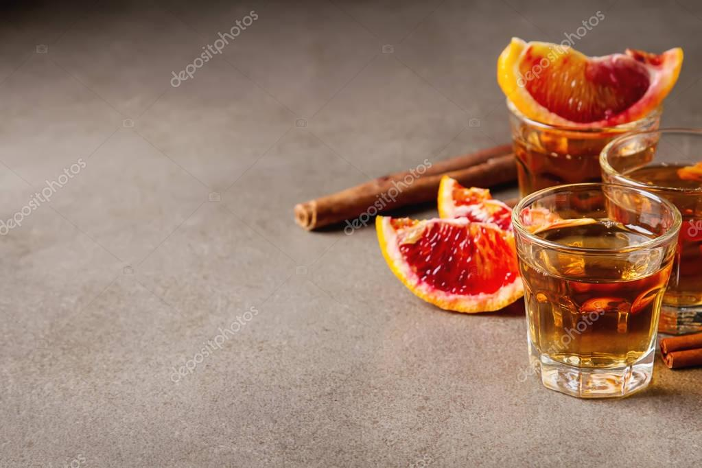 Golden tequila with red orange and cinnamon. Dark background. Se