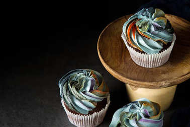 cupcakes on a wooden board. Sweet dessert for a birthday. Dark background