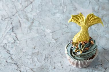 cupcakes berry with tail of a mermaid of mastics. Sweet dessert for a birthday. Dark background