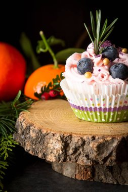cupcakes berry and chocolate on a wooden board. Sweet dessert with tangerines. Dark background