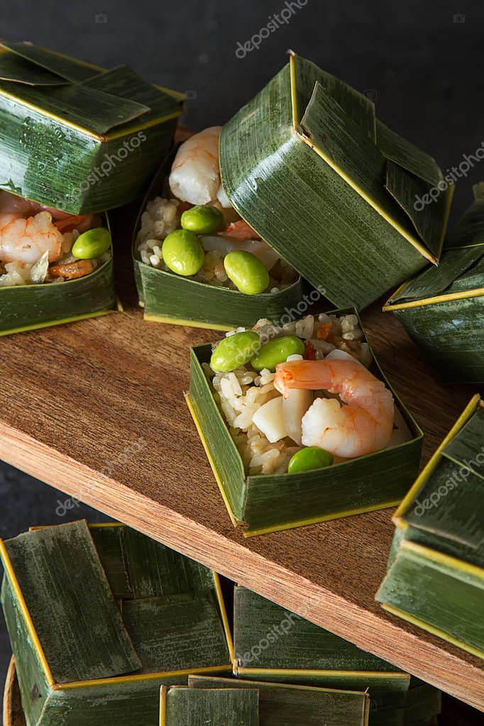 Prawn parsels with shrimps in banana leaves. Dark background. Asian cuisine