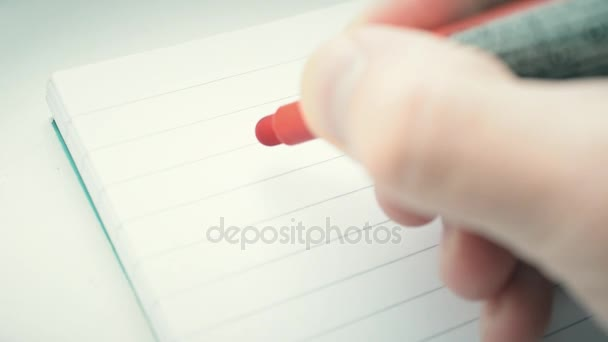 Mano che scrive la parola obiettivo con lindicatore rosso nel blocco note