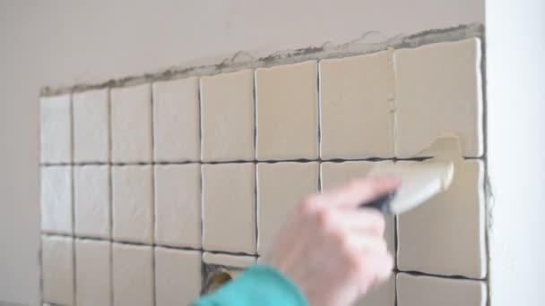 Lavoratore riempire le lacune tra le piastrelle con fughe di