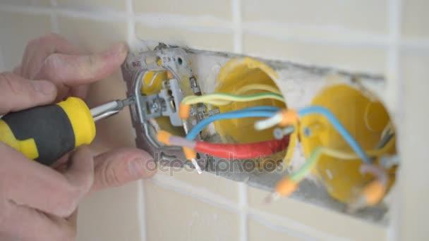 Elektrikář ruce instalace kabelové elektrické zapojit do zdi
