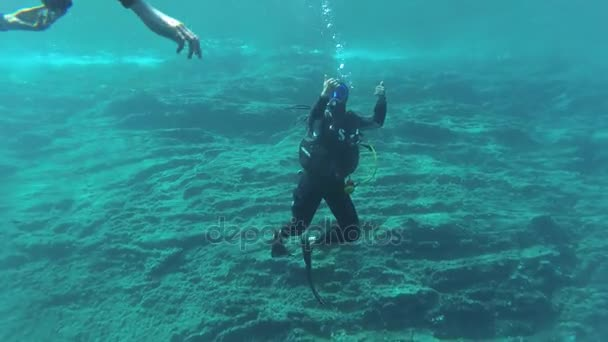 Diving instructor communicates vith other divers using gestures