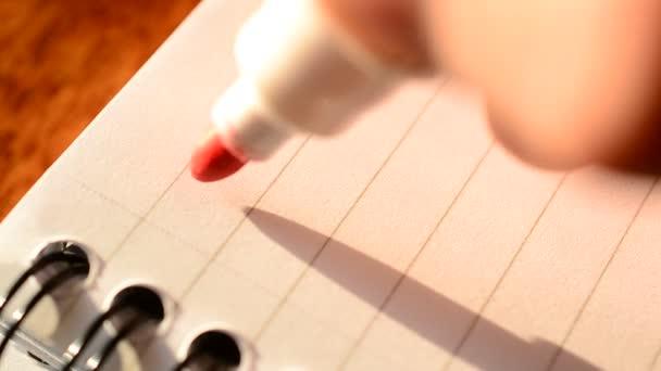Mano che scrive la parola obiettivi con lindicatore rosso nel blocco note
