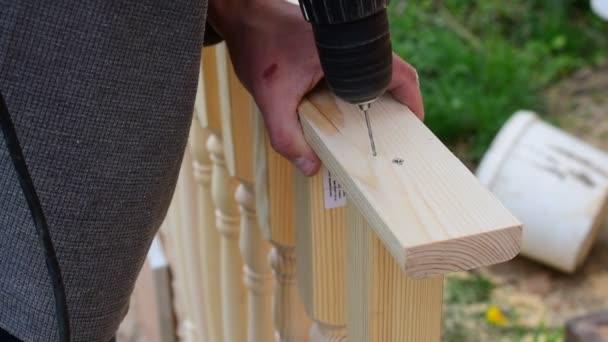 Rukou Carpenter vrtání s vrtačkou v zábradlí