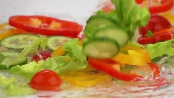 Výseče zralé zeleniny klesá na tabulce s vodou. Zpomalený pohyb
