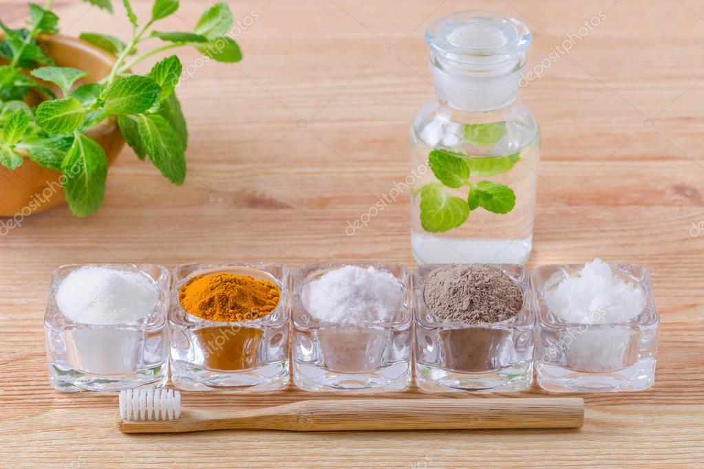 alternative natural mouthwash with mint, toothpaste xylitol or soda, turmeric - curcuma, himalayan salt, clay or ash, coconut oil and wood toothbrush, on wooden