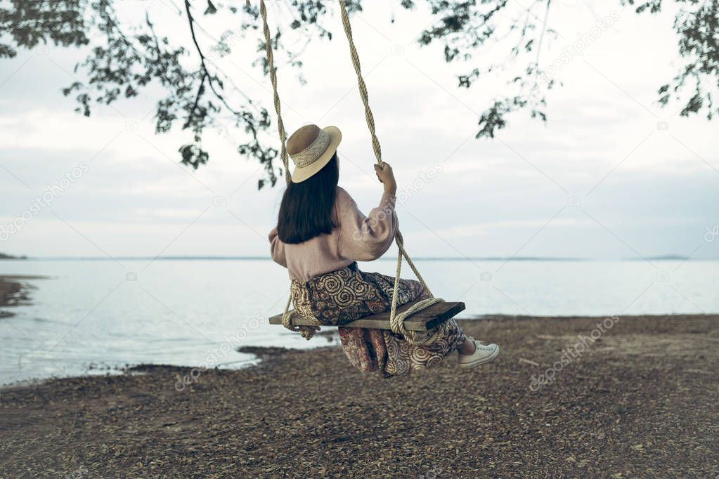 Lifestyle of woman happy relaxing with swing at riverside.