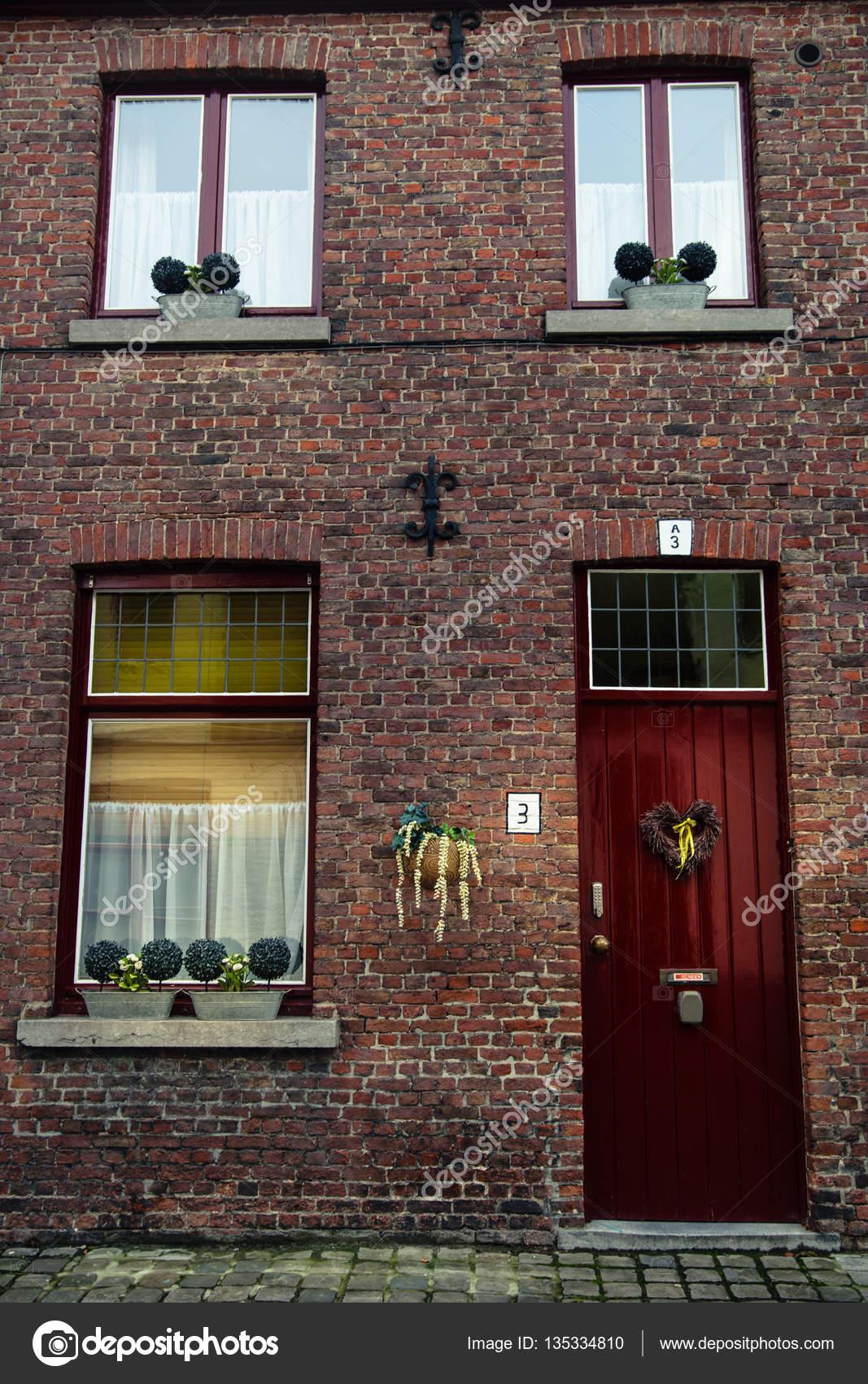 Drie rode houten ramen met witte gordijnen en deur met hartvormige ...