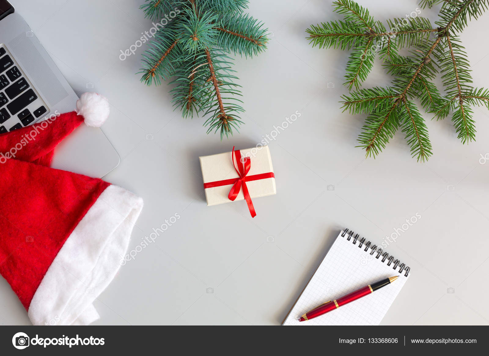 Top View Of Grey Office Table With Cropped Laptop And Christmas Theme Items Branch New Year Tree Santa Cap Notepad Pen Decorated Gift Box Photo By