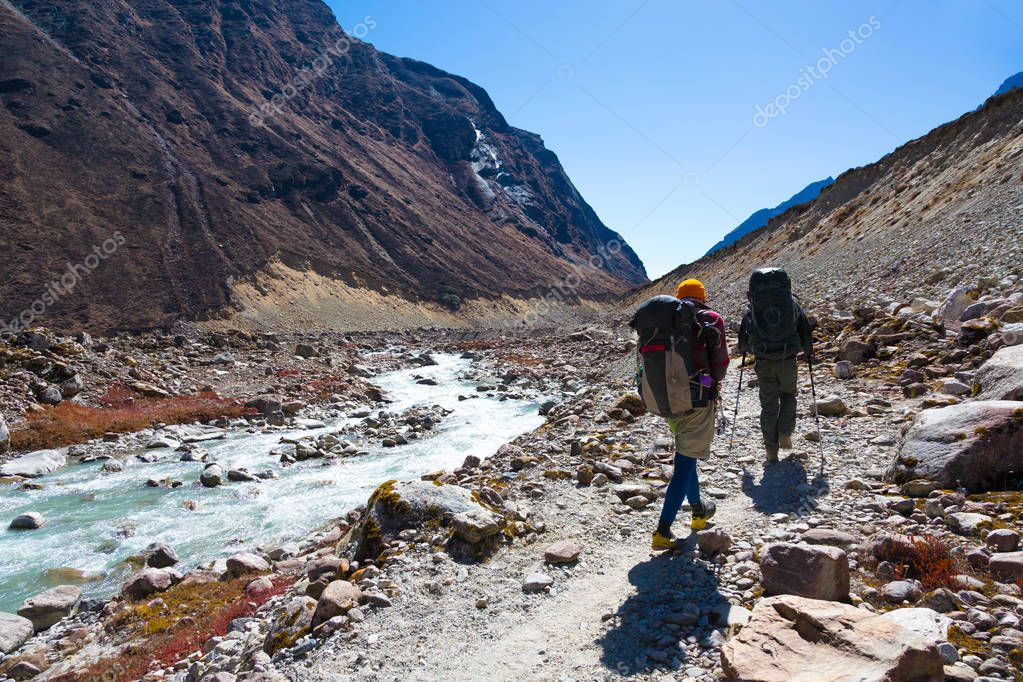 People walking along Creek with Backpacks