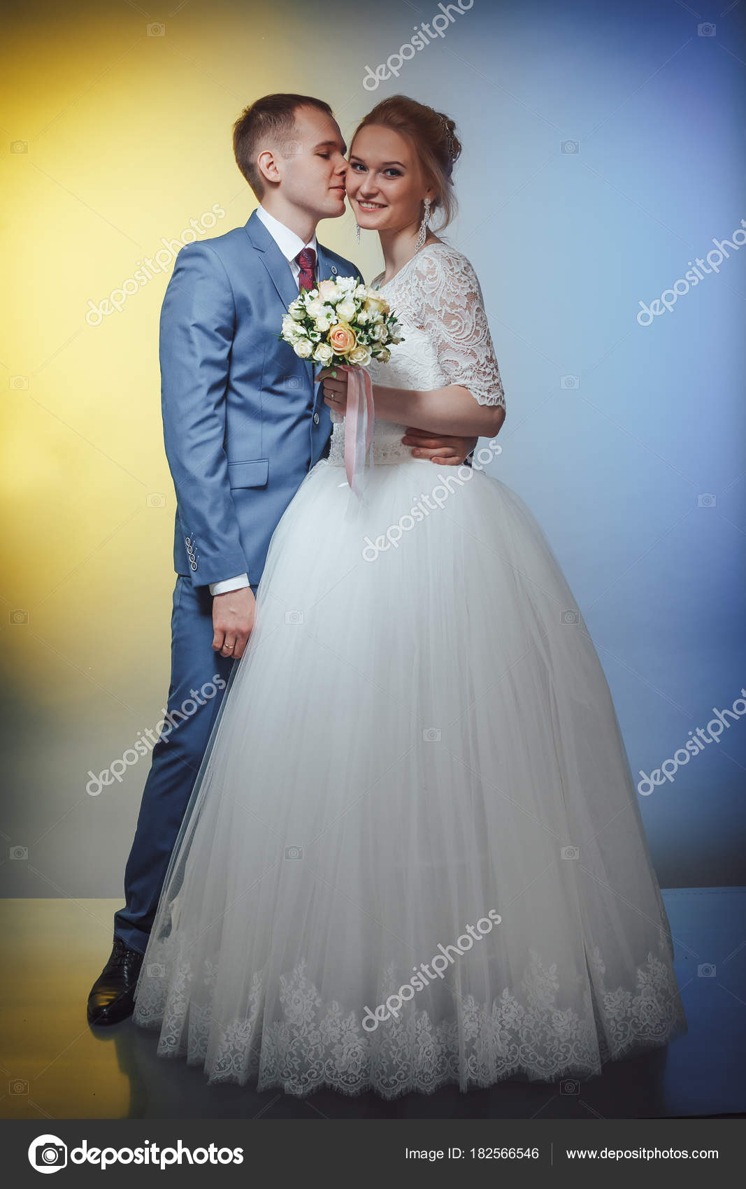Beautiful bride in a white dress and a young groom in a blue suit in ...