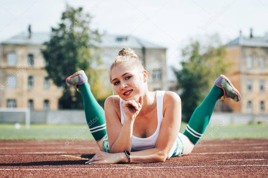 Female athlete does sport exercises in the stadium