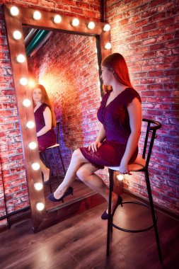 Girl in a burgundy dress in front of a lighted mirror in a dark room. Model posing for a cam during photoshoot in the Studio