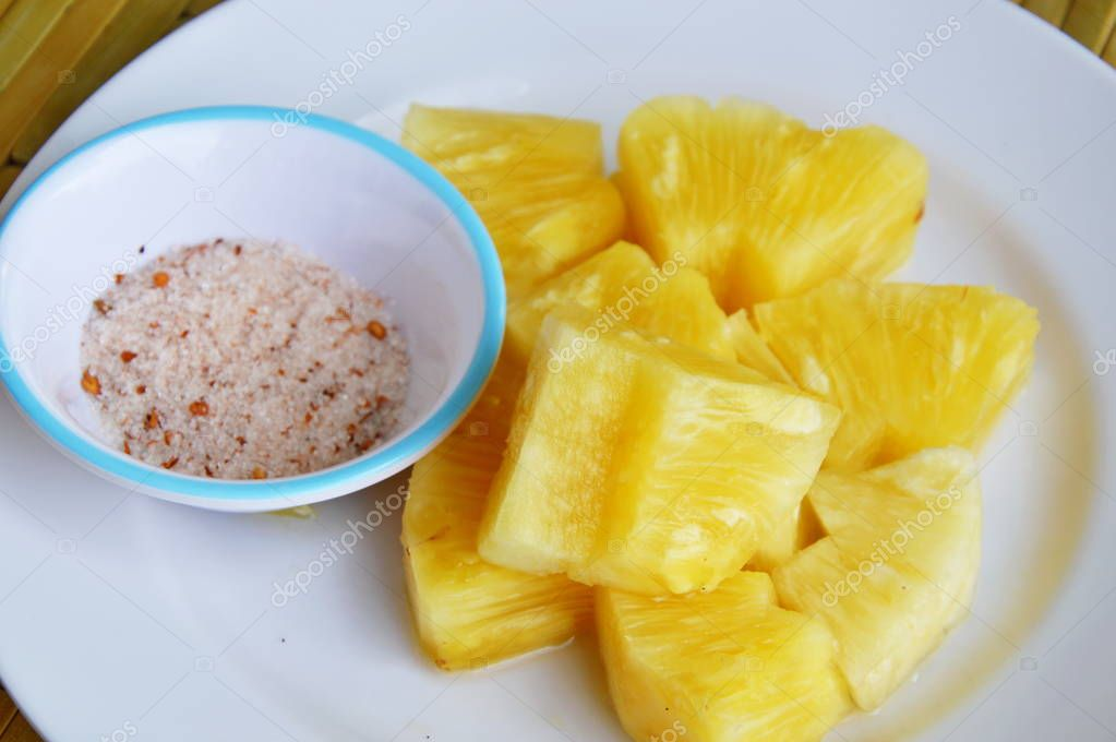 pineapple slice dipping with mixed sugar salt and pepper on white plate