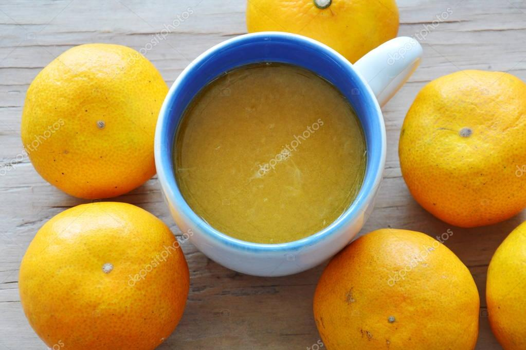 orange juice in cup and tangerine on wooden table