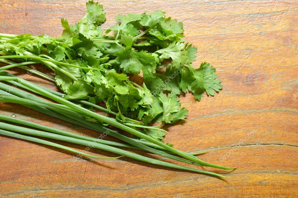 fresh parsley and spring onion arranged on wooden table