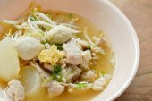 Fotografie gekochtes Stück Schweinefleisch und Ball mit Bean Sprout in klare Suppe auf Schüssel