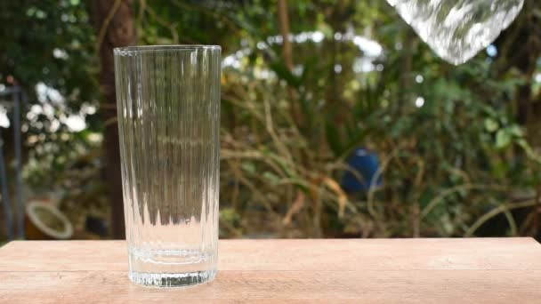 water pouring from bottle in drinking glass on garden background