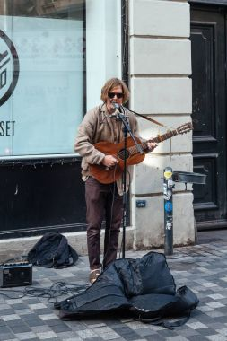 Busker playing guitar and singing in pedestrian street in Copenh